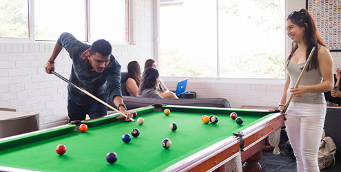 Two students playing pool