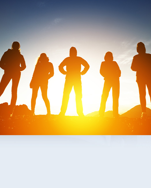 Five young people silhouetted against sun rise