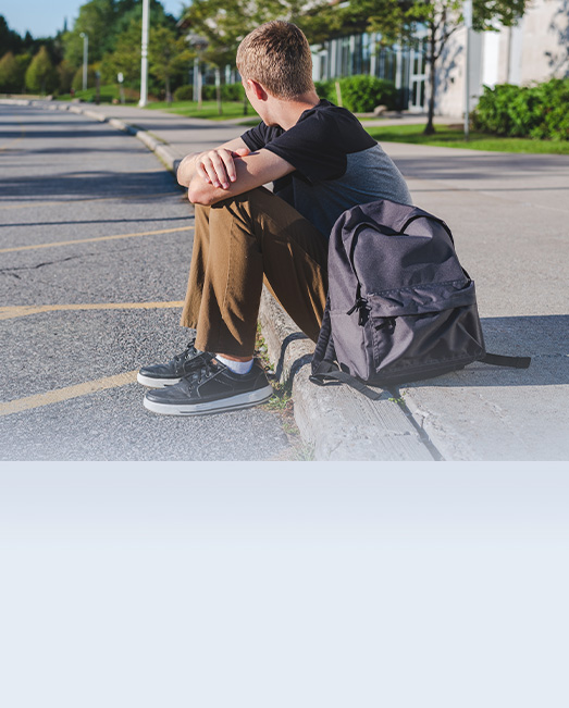 A teenage boy alone and waiting on a roadside curb.