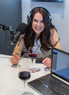 Victoria Devine sitting at a table with microphone, computer and red wine for podcast